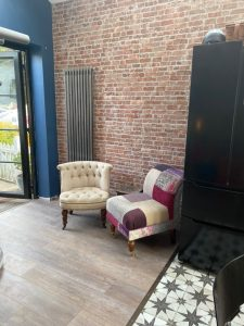 exposed brick, wooden floors and raw metal vertical radiator