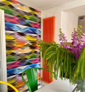 Spring coloured column rads - Orange vertical column radiator agains a geometric multicoloured wall